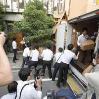 Officials from the Osaka District Public Prosecutors' Office carry seized items in a raid at the Moritomo Gakuen head office in Osaka on Tuesday. | KYODO