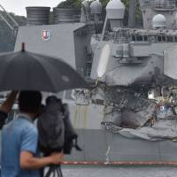 A TV crew films the damage to the guided missile destroyer USS Fitzgerald at its mother port in Yokosuka, Kanagawa Prefecture, Sunday. A number of missing American sailors have been found dead in flooded areas of a destroyer that collided with a container ship off Japan's coast, the U.S. Navy said on Sunday. | AFP-JIJI