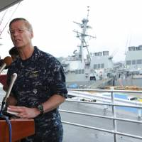 Vice Adm. Joseph Aucoin, commander of the U.S. 7th Fleet, speaks during a press conference on the status of the USS Fitzgerald (seen at the rear) and search and rescue efforts for seven missing Fitzgerald crew members, at the U.S. Naval base in Yokosuka, Kanagawa Prefecture, Sunday. | AP
