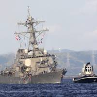The damaged USS Fitzgerald is being towed by a tugboat near the U.S. Naval base in Yokosuka, Kanagawa Prefecture, after the U.S. destroyer collided with the Philippine-registered container ship ACX Crystal in the waters off the Izu Peninsula Saturday. | AP