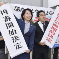 Lawyers hold up signs announcing a decision Wednesday by the Kagoshima District Court to retry a woman convicted in a 1979 murder case. | KYODO