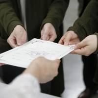 A same-sex couple receives a certificate recognizing their partnership at Sapporo City Hall on Thursday. | KYODO