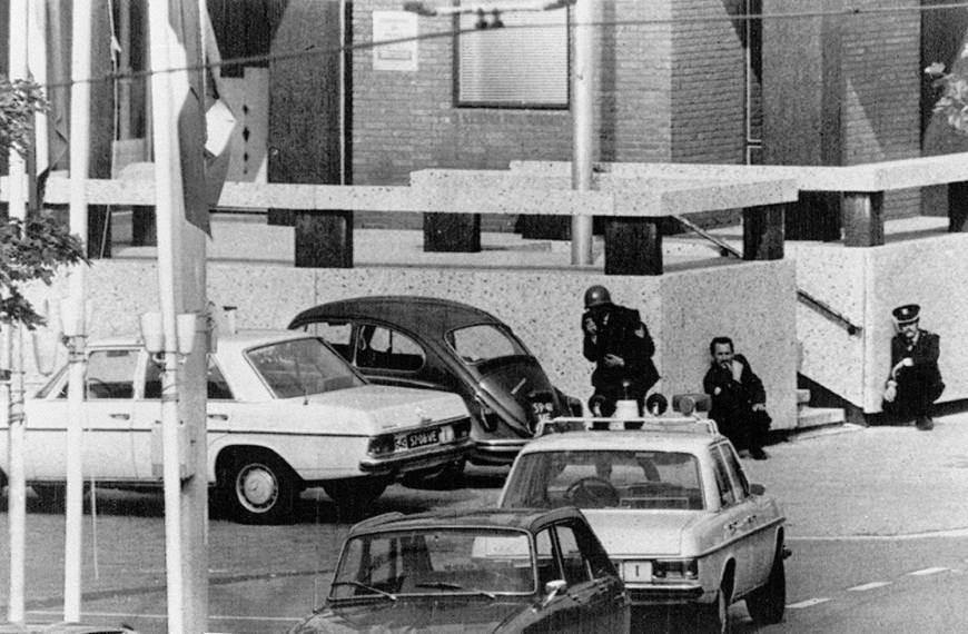 Police crouch against a wall at the French Embassy in The Hague where hostages were held by Japanese Red Army guerillas in September 1974.