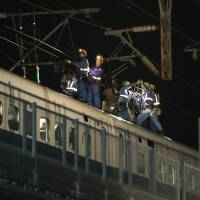 Railway workers repair a disconnected overhead power line on the outbound line early Thursday in Takatsuki, Osaka Prefecture. | KYODO