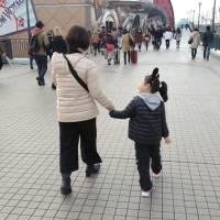 Mari Takada, a representative of a Tokyo-based organization that provides information and support for single mothers by choice, walks with her child in this undated photo. | COURTESY OF MARI TAKADA / VIA KYODO