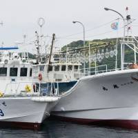 A coast guard patrol boat docks next to another boat Thursday at the Nagoya port in Karatsu, Saga Prefecture. A record 206 kg of smuggled gold was found from the boat. | KYODO