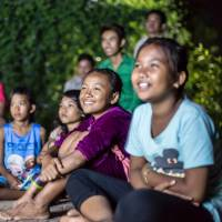 Children watch a film by the Tokyo-based nonprofit organization World Theater Project in a farming village in Battambang province, Cambodia, in December 2015.   COURTESY OF WORLD THEATER PROJECT / VIA KYODO