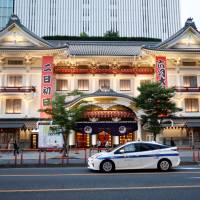 A Toyota Prius hybrid taxi drives past a kabuki theater in Tokyo on Tuesday.   REUTERS