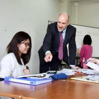 Benjamin Peters, vice president of Miyazaki International College, teaches a political science class in May. | KYODO