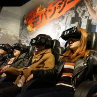 Visitors experience the Ultra Reverse Bungee game with virtual reality headsets and moving seats at Shibuya VR Land in Tokyo. | COURTESY OF HUIS TEN BOSCH CO.