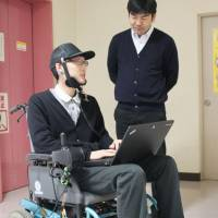 Makoto Sasaki (right), an assistant professor at Iwate University, helps test a wheelchair that can be operated by the user's tongue movements. | KYODO