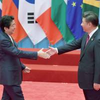 Chinese President Xi Jinping greets Prime Minister Shinzo Abe during the Group of 20 summit in China in September 2016. | KYODO