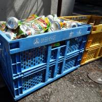 Cans and bottles are separated into specific recycling crates and left by the side of the road for collection in Tokyo's Setagaya Ward. | TIM HORNYAK