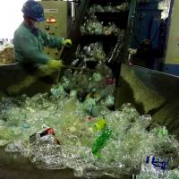 PET bottles are put into a compressor at the Minato Resource Recycle Center in Tokyo. | TIM HORNYAK