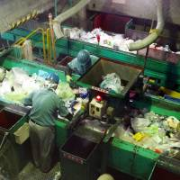 Workers sort plastic waste at the Minato Resource Recycle Center in Tokyo. | TIM HORNYAK