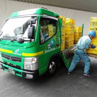 Crates of bottles are unloaded at the Minato Resource Recycle Center in Tokyo. | TIM HORNYAK