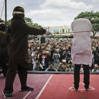 A Shariah law official whips one of two men convicted of gay sex during a public caning outside a mosque in Banda Aceh, the capital of Indonesia's Aceh province. | AP