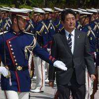 Prime Minister Shinzo Abe, shown reviewing an honor guard at a Tuesday ceremony to mark the return of SDF peacekeepers, is on an ideological mission to reshape the Japanese state. | AFP-JIJI