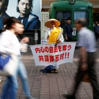 Thought crime: A monk holds a placard protesting what has become known as the conspiracy bill in front of Shibuya Station on Friday. The slogan reads, 'Opposed to the conspiracy law, which deprives freedom of the mind.' | REUTERS