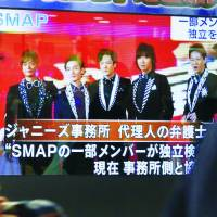 Farewell Johnny: Passersby watch the news of SMAP's breakup on a TV screen in 2016 in Tokyo. | KYODO