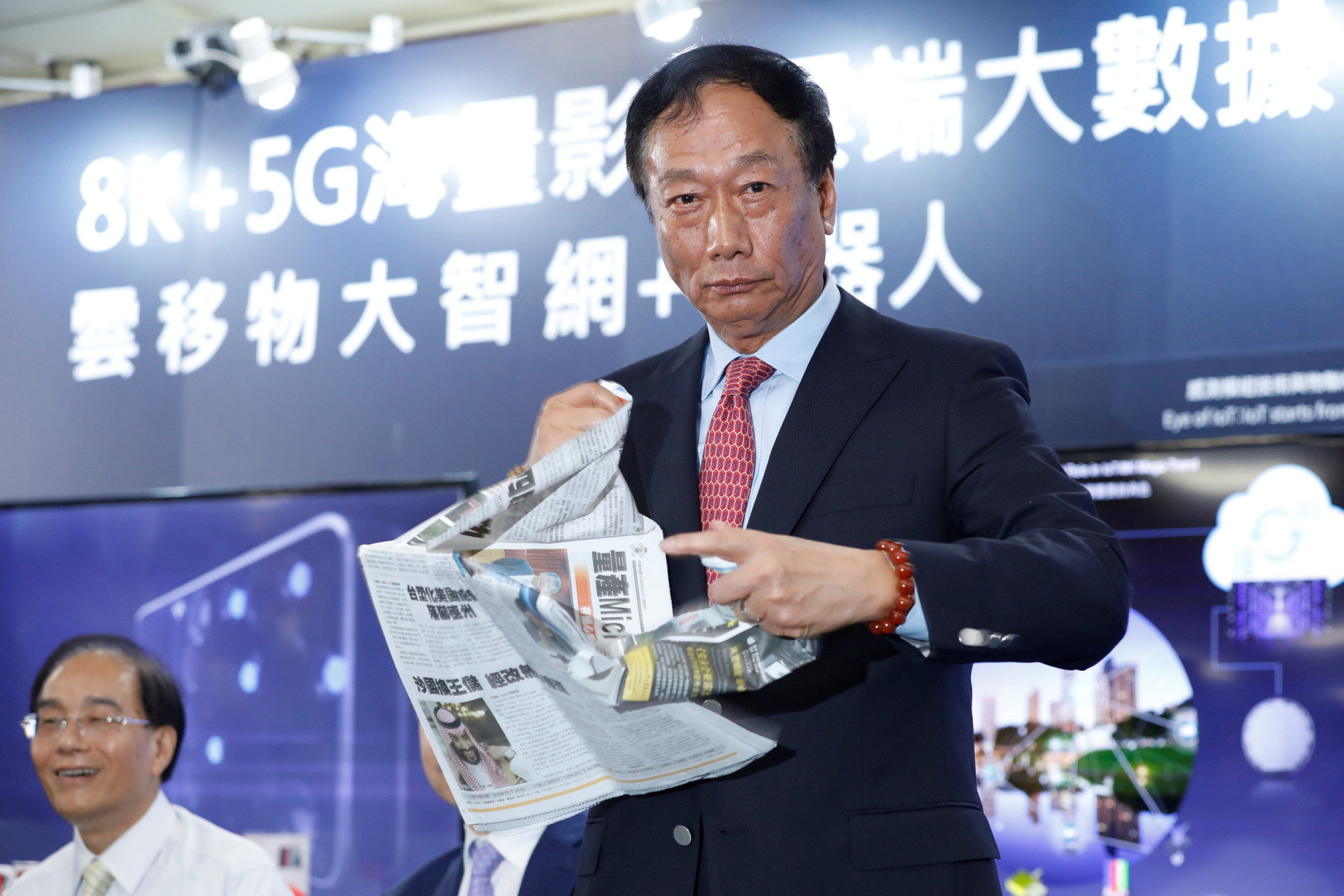 Foxconn Chairman Terry Gou tears up a newspaper bearing a front-page article about Foxconn's losing bid for Toshiba Corp.'s chip unit on June 22, saying the pursuit isn't over. | REUTERS
