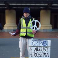 An anti-nuclear activist hands out peace cranes in Wellington on Aug. 6, 2014. | WILLIAM STADTWALD DEMCHICK