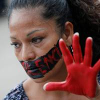 An activist takes part in a demonstration against the killing of Mexican journalists  in Mexico City on May 30. The words painted across her face read: 'No to Silence.' Since 1992, 41 Mexican journalists have been killed and another 50 have died in murky circumstances. | REUTERS