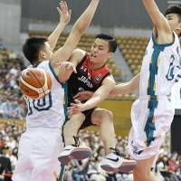 Yuki Togashi passes the ball around a Macau defender during Japan's 119-47 win at the East Asia Basketball Championship in Nagano on Sunday. | KYODO