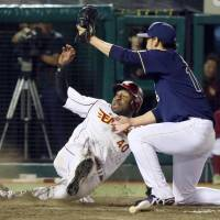 Tohoku Rakuten's Zealous Wheeler slides home to score in the ninth inning of the Eagles 4-4 tie with the Buffaloes on Monday night. | KYODO