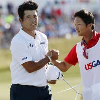 Hideki Matsuyama is congratulated by his caddie following his round on the final day of the U.S. Open on Sunday. | KYODO