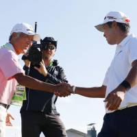 Hideki Matsuyama is greeted by Isao Aoki (left) during the U.S. Open on Sunday. Matsuyama finished tied for second. | KYODO