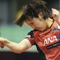 Miu Hirano hits a shot during her match against Chen Meng in the Japan Open quarterfinals on Saturday. Below: Hirano reacts during her 7-11, 8-11, 5-11, 7-11 loss. | AP
