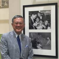 Masanori Murakami poses in front of photos of himself at the Pacific Pitch: U.S.-Japan Baseball Diplomacy exhibition Thursday at Tokyo Metropolitan Central Library on Thursday. | JASON COSKREY
