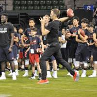 NFL legend Tom Brady demonstrates his passing skills on Wednesday. | HIROSHI IKEZAWA