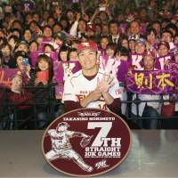 As fans smile behind him, Tohoku Rakuten right-hander Takahiro Norimoto poses with a sign to commemorate his seventh straight game with 10 or more strikeouts on Thursday night at Kobo Park. Norimoto broke Hideo Nomo's NPB record of six consecutive games, which was set in 1991. | KYODO