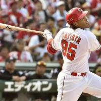 Hiroshima's Xavier Batista hits a two-run home run in the sixth inning of the Carp's 6-5 win over the Marines on Saturday. | KYODO