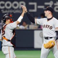Yomiuri Giants catcher Seiji Kobayashi and reliever Scott Mathieson celebrate the team's 2-1 victory over the Hokkaido Nippon Ham Fighters on Friday night at Sapporo Dome. | KYODO