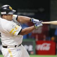 Fukuoka SoftBank's Alfredo Despaigne hits a tie-breaking home run in the eighth inning of the Hawks' 6-5 win over the Fighters on Wednesday night. | KYODO