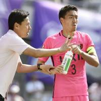 Kashima Antlers manager Go Oiwa (left) gives instructions to defender Gen Shoji during their 3-1 win over Sanfrecce Hiroshima in the J. League on Sunday. | KYODO