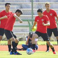 Japan's Yasuyuki Konno (left) and Yuya Kubo compete for the ball during a training session in Tehran on Sunday. | KYODO