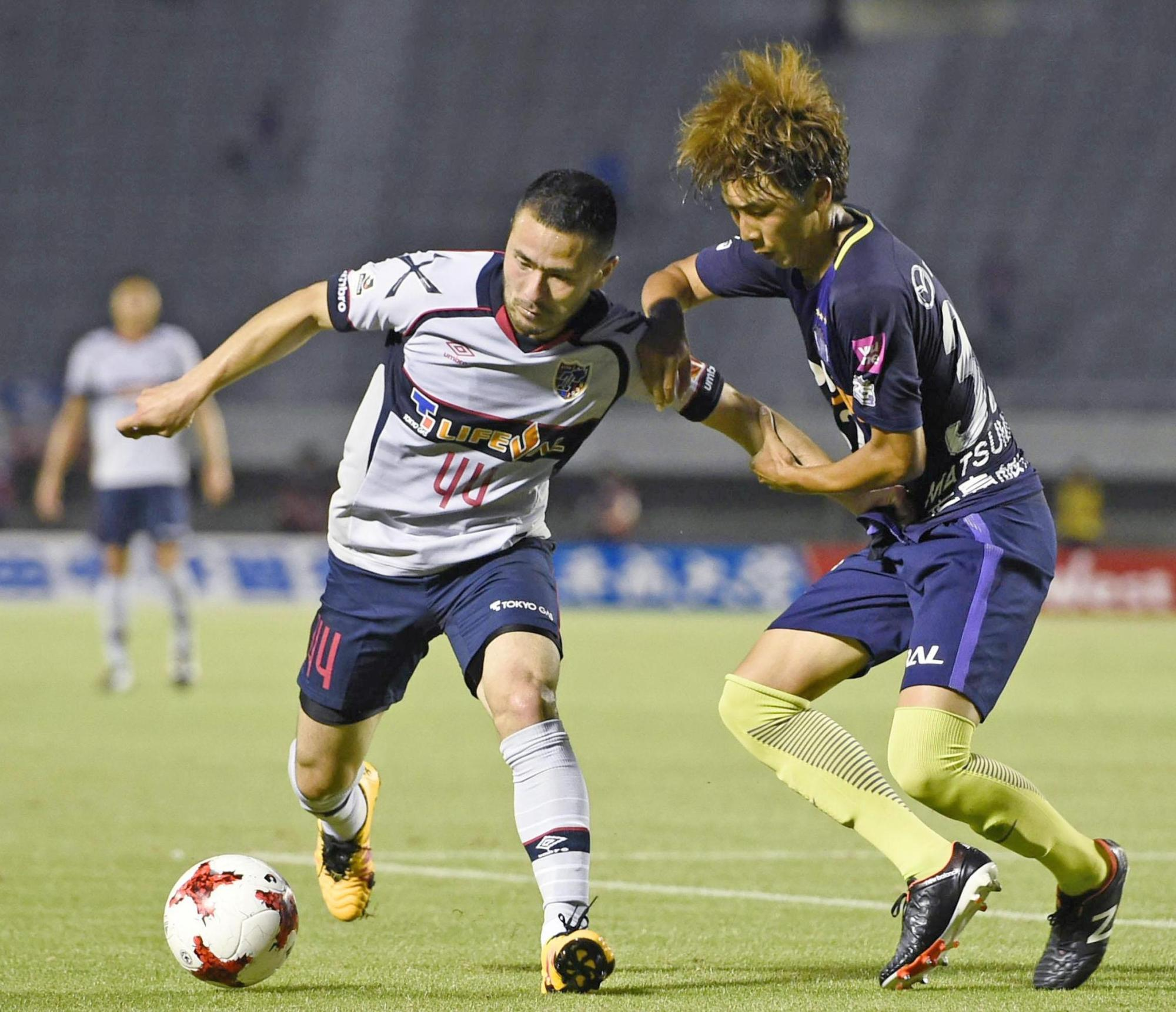 FC Tokyo's Takuma Abe (left) holds off Sanfrecce Hiroshima's Taishi Matsumoto during their J. League Cup playoff first-leg match on Wednesday. | KYODO