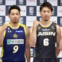 Brex guard Yusuke Endo (left) and SeaHorses guard Makoto Hiejima pose for photos at a Tokyo news conference on Monday. Their teams will face each other on the opening weekend of the B. League 2017-18 season. | KAZ NAGATSUKA