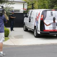 A television cameraman shoots video across from the front gate of a home belonging to Cleveland Cavaliers' LeBron James Wednesday in Los Angeles. Police are investigating after someone spray-painted a racial slur on the front gate of James' home in Los Angeles on the eve of the NBA Finals. | AP
