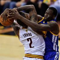 Warriors forward Draymond Green (right) contests a shot attempt by Cavaliers guard Kyrie Irving during Game 4 of the NBA Finals on Friday. | USA TODAY / VIA REUTERS