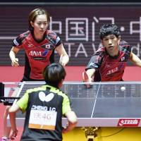 Japan's Maharu Yoshimura (rear, right) plays a shot alongside mixed doubles partner Kasumi Ishikawa at the Table Tennis World Championships last week in Dusseldorf, Germany. | KYODO
