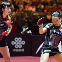 Mima Ito plays a shot as doubles partner Hina Hayata watches on during their Table Tennis World Championships semifinal against China's Ding Ning and Liu Shiwen on Monday. | KYODO