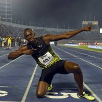 Usain Bolt strikes his trademark victory pose after winning the 100-meter race at the Racers Grand Prix in Kingston on Saturday. | AFP-JIJI