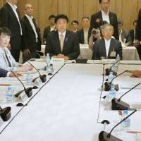 Members of the government's economic policy panel gather at the Prime Minister's Office on Friday evening to discuss next year's budget. | KYODO