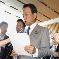 Finance Minister Taro Aso announces Friday the government's decision to impose emergency tariffs on frozen beef from the United States and other sources from August.   KYODO