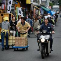 A man rides a Honda Motor Co. Super Cub at the Tsukiji market in Tokyo on June 13. | BLOOMBERG